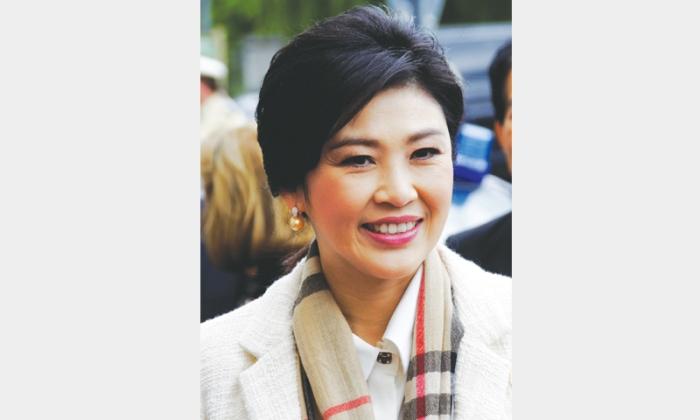 Former Thai PM returns home as legal threat lingers