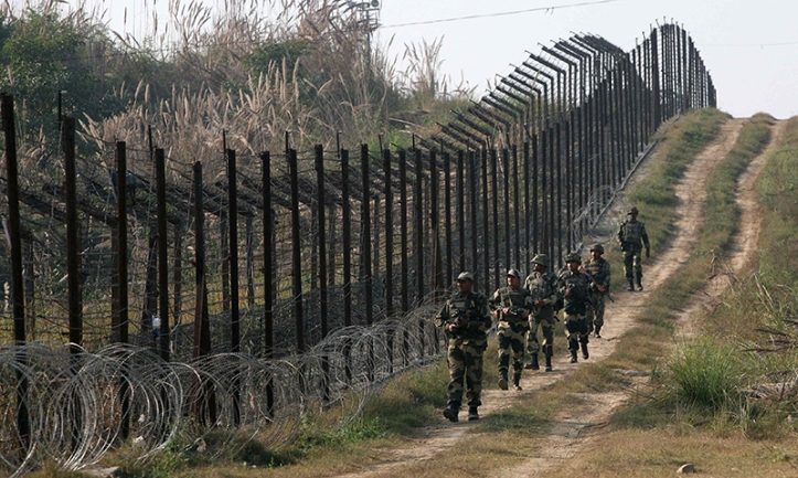 Indian BSF soldiers patrol the fenced border with Pakistan at Babiya village