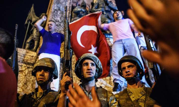 Turkish solders stay at Taksim square as people react in Istanbul on July 16, 2016.  Turkish military forces on July 16 opened fire on crowds gathered in Istanbul following a coup attempt, causing casualties, an AFP photographer said. The soldiers opened fire on grounds around the first bridge across the Bosphorus dividing Europe and Asia, said the photographer, who saw wounded people being taken to ambulances.  / AFP PHOTO / OZAN KOSE