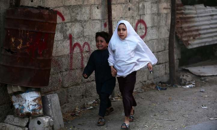 TOPSHOT - Syrian children run for cover following a reported airstrike on Kafr Batna, in the rebel-held Eastern Ghouta area, on the outskirts of the capital Damascus, on September 30, 2016. Air raids on several rebel-held towns in the Eastern Ghouta region killed at least 17 people including eight children, the Syrian Observatory for Human Rights monitor said. / AFP PHOTO / AMER ALMOHIBANY