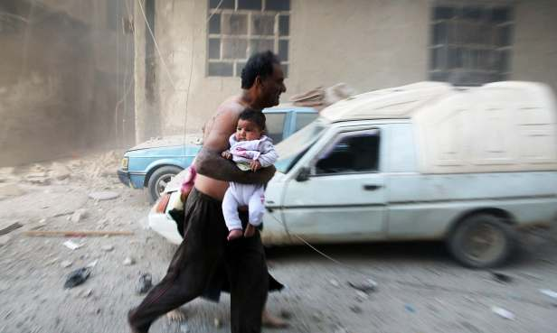 TOPSHOT - A Syrian man carrying a child emerges from a dust cloud following a reported airstrike on Kafr Batna, in the rebel-held Eastern Ghouta area, on the outskirts of the capital Damascus, on September 30, 2016. Air raids on several rebel-held towns in the Eastern Ghouta region killed at least 17 people including eight children, the Syrian Observatory for Human Rights monitor said. / AFP PHOTO / AMER ALMOHIBANY