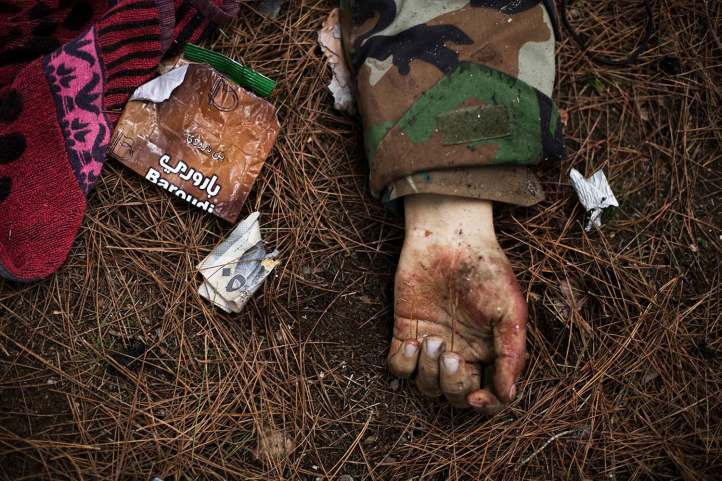 The body of a Syrian Army soldier lies on the ground after heavy clashes with government forces at a military academy besieged by the rebels in Tal Sheer, Syria, Sunday, Dec. 16, 2012. (AP Photo/Manu Brabo, File)