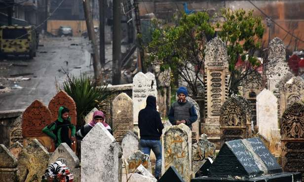 Syrian residents stand in a graveyard in Aleppo's Al-Kalasseh neighbourhood that was newly captured by pro-governments forces in the eastern part of the war torn city on December 13, 2016. / AFP PHOTO / George OURFALIAN