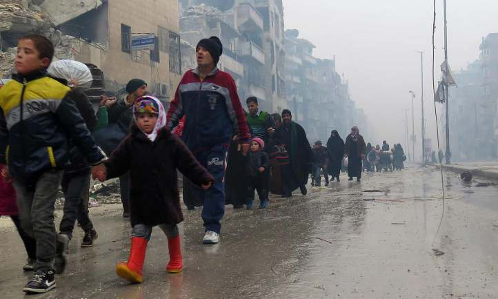 Syrian residents, fleeing violence in the restive Bustan al-Qasr neighbourhood, arrive in Aleppo's Fardos neighbourhood on December 13, 2016, after regime troops retook the area from rebel fighters.  Syrian rebels withdrew from six more neighbourhoods in their one-time bastion of east Aleppo in the face of advancing government troops, the Syrian Observatory for Human Rights said. / AFP PHOTO / STRINGER