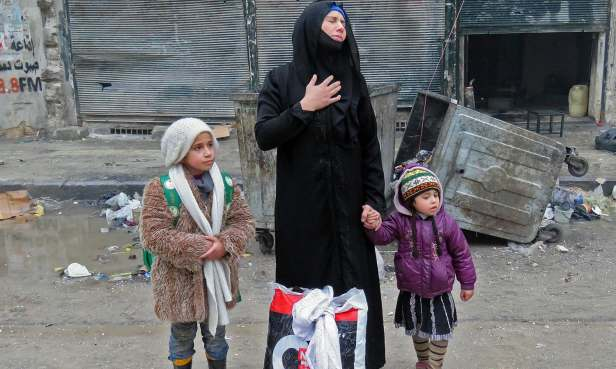 A Syrian woman, fleeing violence in the restive Bustan al-Qasr neighbourhood, reacts as she stands with her children in Aleppo's Fardos neighbourhood on December 13, 2016, after regime troops retook the area from rebel fighters.  Syrian rebels withdrew from six more neighbourhoods in their one-time bastion of east Aleppo in the face of advancing government troops, the Syrian Observatory for Human Rights said. / AFP PHOTO / STRINGER