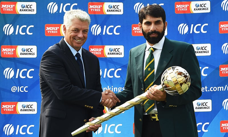 Pakistan cricket captain Misbah-ul-Haq (R) receives a ICC Test Championship mace from ICC Chief Executive David Richardson in Lahore on September 21, 2016.